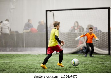 MOSCOW, RUSSIA - JAN 27, 2018: Forward attacks opponent goal during children sport clubs cup soccer game at indoor sports ground of Krasnaya Presnya stadium.