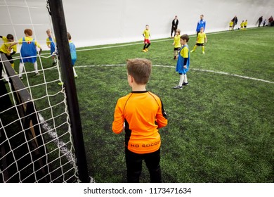 MOSCOW, RUSSIA - JAN 27, 2018: Goalkeeper at goal post and players during children sport clubs cup soccer game at indoor sports ground of Krasnaya Presnya stadium.