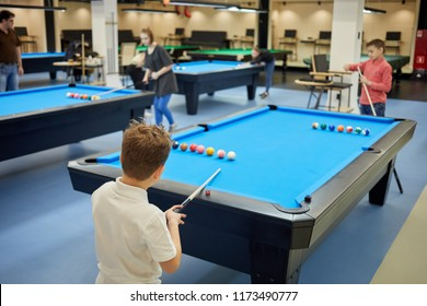MOSCOW, RUSSIA - JAN 27, 2018: Billiards room with tables and players in Pool School, focus on boy in white shirt, rear view. Main mission of School is the popularization of billiard sports.