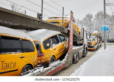 MOSCOW, RUSSIA - JAN 31, 2018: Car transporter trucks with Yandex Taxi cars on city winter road.