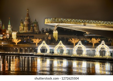 MOSCOW, RUSSIA  - January 01, 2019 Festive Pier with hovering bridge of Zaryadye Park in background of St. Basil's Cathedral on New Year's Eve. View from Raushskaya embankment of Moscow River.