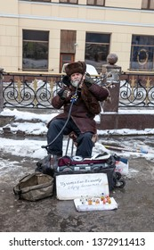 MOSCOW, RUSSIA - January 02.2013: A street musician plays the bagpipes. On the poster inscription  Will produce the bagpipes, I will teach you to play