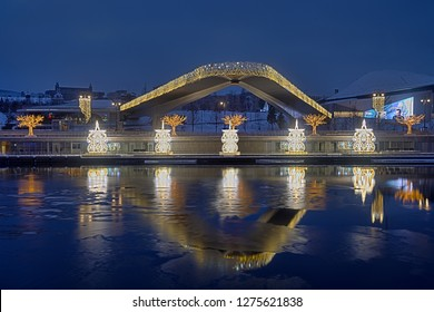 MOSCOW, RUSSIA - January 05, 2019 Festively decorated for winter holidays the pier on MOskvoretskaya embankment of river Moskva (Moscow) and hovering bridge of Zaryadye Park in morning twilight.