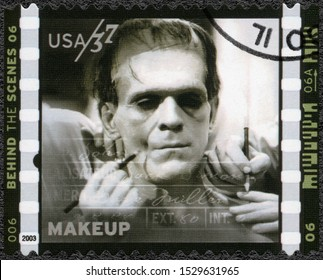 MOSCOW, RUSSIA - JANUARY 09, 2018: A stamp printed in USA shows Makeup Jack Pierce working on Boris Karloff for Frankenstein, American Filmmaking Behind the Scenes, 2003