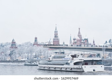 """MOSCOW, RUSSIA - JANUARY 11, 2020: The """"floating bridge"""" of the park """"Zaryadye"""", Moscow Kremlin and Radisson Royal Flotilla yacht on Moskva-river in winter day"""