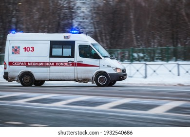 Moscow, Russia - January 14 2021: An ambulance with flashing lights on is driving along the street. Snow is all around. Side view, motion blur. Residential area. Translation: Ambulance