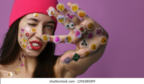 Moscow, Russia - January 15, 2019: Young woman with popular social mobile emoji smiles stickers for cellphone android or iPhone on her hand show peace sign on purple background