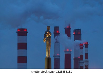 Moscow, Russia - January 16, 2020: Industrial silhouettes of Moscow city. Yury Gagarin monument in Moscow in winter blue sunset. Heat station pipes are nearby. Long exposure photography.