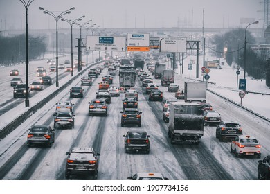 Moscow, Russia - January 16 2021: Traffic jam on the Moscow Ring Road. In opposite direction the road is clear. Cloudy winter day. Road and cars are covered with snow. Translation: road signs, pallets