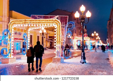 Moscow, Russia, January 17, 2018. Night winter Moscow in the snow. Street Old Arbat decorated for the New year. Unidentified people walking on the street.