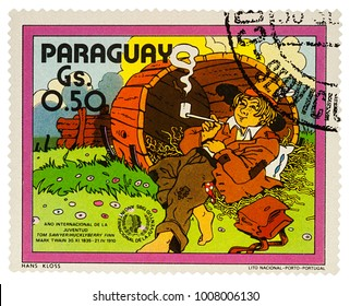 """Moscow, Russia - January 18, 2018: A stamp printed in Paraguay shows Huckleberry Finn in the old barrel, Adventures of Tom Sawyer by Mark Twain, series """"International Year of Youth"""", circa 1985"""