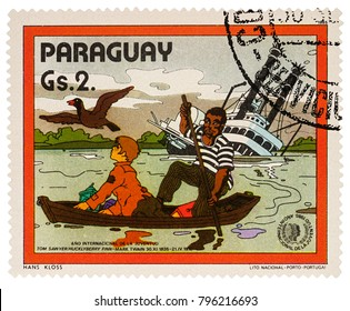 """Moscow, Russia - January 18, 2018: stamp printed in Paraguay shows Finn and Joe in boat near Sinking Riverboat, Adventures of Tom Sawyer by Mark Twain, series """"International Year of Youth"""", circa 1985"""