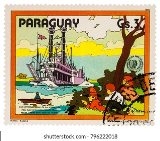 """Moscow, Russia - January 18, 2018: stamp printed in Paraguay shows Finn, Friends and Riverboat on Mississippi, Adventures of Tom Sawyer by Mark Twain, series """"International Year of Youth"""", circa 1985"""
