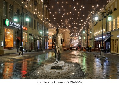 MOSCOW, RUSSIA - January 18, 2018 Bronze monument to tremarkable Russian composer Sergei Prokofiev between old-style streetlamps on Kamergersky Lane under lights of hundreds of bulbs at night