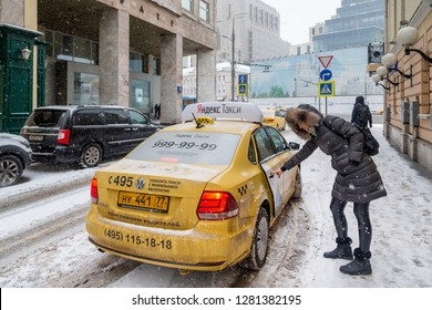 MOSCOW, RUSSIA - JANUARY 2, 2019: Passenger getting into Yandex taxi in Moscow during winter season