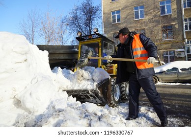 MOSCOW, RUSSIA - January , 2015: Man with a shovel and bulldozer cleaning snow. Cleaning the streets of the city in winter in Moscow.