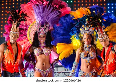 MOSCOW, RUSSIA- JANUARY 2017: Brazilian carnival show. Beautiful girls and boys bright colorful carnival costume on stage. Smiling afro-americans women and men samba dancer couples on dance floor