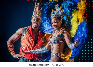 MOSCOW, RUSSIA- JANUARY 2017: Brazilian carnival show. Beautiful girl and boy bright colorful carnival costume on stage. Smiling afro-americans woman and man samba dancer couple on dance floor