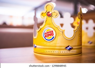 Moscow, Russia - January 2019: Burger King Logo On Crown. Paper Burger King Crown On Wooden Table Surface On Interior Fast Food Restaurant Background.
