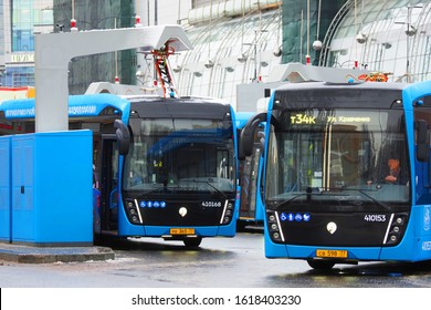 Moscow,  Russia - January, 2020:  Blue electric bus at a stop is charged by pantograph. Electric bus charging station