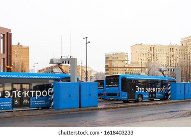 Moscow,  Russia - January, 2020: Electric bus charging station. Blue electric bus at a stop is charged by pantograph