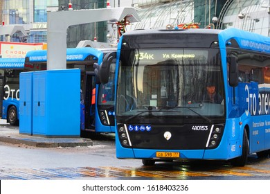 Moscow,  Russia - January, 2020:  Electric bus leaves the charging station. Blue electric bus at a stop is charged by pantograph