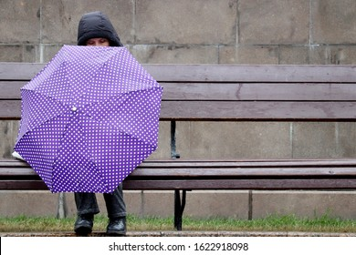 Moscow, Russia - January 2020: Rain in a city, woman with lilac umbrella and jacket with hood sitting on a wooden bench. Rainy weather, concept of loneliness, sadness, depression