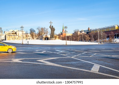 MOSCOW, RUSSIA - JANUARY 25, 2019: taxi at Borovitskaya Square near Monument to Vladimir the Great and Kremlin in Moscow city in sunny winter day. Monument was designed by Salavat Scherbakov