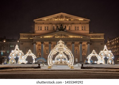 MOSCOW, RUSSIA - January 27, 2019 Beautiful New Year decorations at Theater Square in early dark winter morning in the background of the famous Bolshoi Theater building during a heavy snowfall.