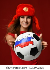 Moscow, Russia - January 29, 2018: Russian style fan sport woman player in red uniform and ear flaps hat with double-headed eagle give soccer ball celebrating happy smiling on red background