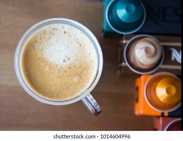 MOSCOW, RUSSIA - JANUARY 31, 2018: Illustrative and Editorial image of Nespresso Boxes and Coffee Capsules on Top of Each Box and Cup Of Coffee on Wooden Background