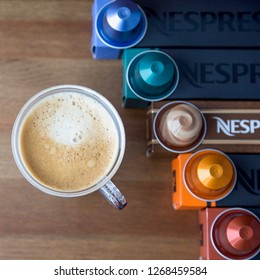 MOSCOW, RUSSIA - JANUARY 31, 2018: Nespresso Boxes and Coffee Capsules on Top of Each Box and Cup Of Coffee on Wooden Background. Nespresso is Worldwide Company of Coffee Products.
