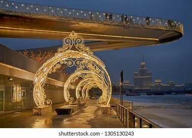 MOSCOW, RUSSIA - January 31, 2019 Pier of Zaryadye Park and hovering bridge at Moskvoretskaya Embankment of Moscow River decorated with beautiful new year arches and garlands in winter twilight.