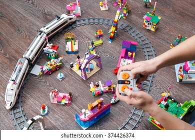 MOSCOW, RUSSIA - January 4, 2016: man hands playing with town built of Lego