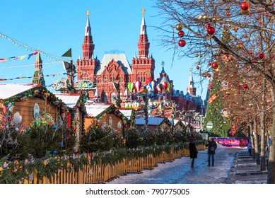 Moscow, Russia - January 9, 2018: New Year and Christmas market and decorations on Red Square. GUM with a Christmas tree and walking people against the background of the Historic museum