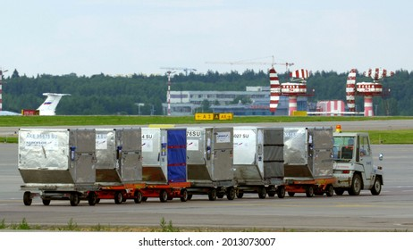 MOSCOW, RUSSIA - JULY 01, 2015: Panning shot of a small truck carrying containers with cargo with following view of an airplane taking off from Sheremetyevo Airport