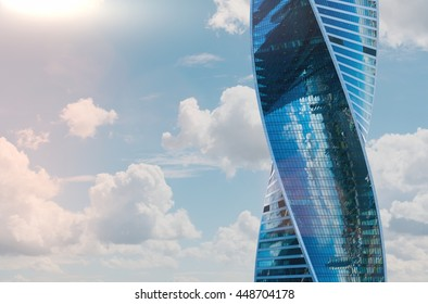 MOSCOW, RUSSIA - JULY 04. Tower in Moscow City center, 04 Jule 2016. ?urved screw skyscraper on the background of the cloudy sky reflects the panorama of the city, bright day, flares