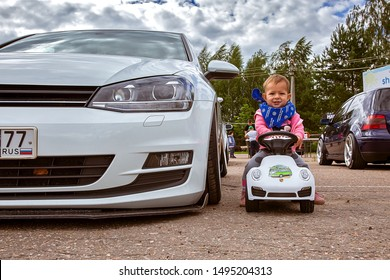 Moscow, Russia: July 06, 2019: Real car Volkswagen golf 7 near baby who sits on a toy vehicle near tuned by low suspension and custom wheels. Ready to race