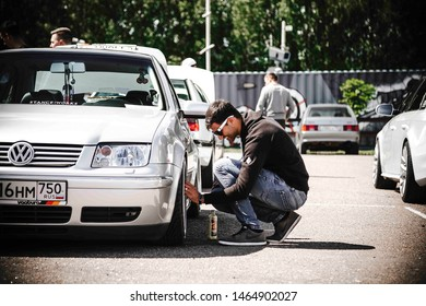 Moscow, Russia - July, 06,2019: A man cleans the wheels of his Volkswagen Bora. Dropped silver car on air suspension.