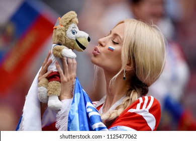 Moscow, Russia - July 1, 2018. Beautiful Russian lady kissing World Cup mascot Zabivaka before FIFA World Cup 2018 Round of 16 match Spain vs Russia.