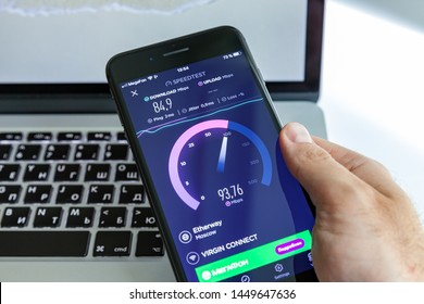 Moscow / Russia - July 13, 2019: Black iPhone 8 Plus in hand on the background of the MacBook. On-screen program SpeedTest