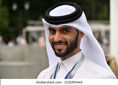 Moscow, Russia - July 14, 2018: Qatari man in traditional clothes looks at the camera and smiles, football stadium in background. Qatar is the successor to Russia in hosting the next World Cup in 2022