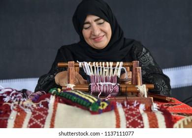 Moscow, Russia - July 14, 2018: A senior arabian woman makes a traditional sadu weaving. Focus on the frame. Qatar