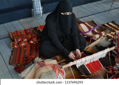 Moscow, Russia - July 14, 2018: A young arabian woman from Qatar makes a traditional sadu weaving.