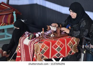 Moscow, Russia - July 14, 2018: A senior and young arabian women make a traditional sadu weaving. Qatar