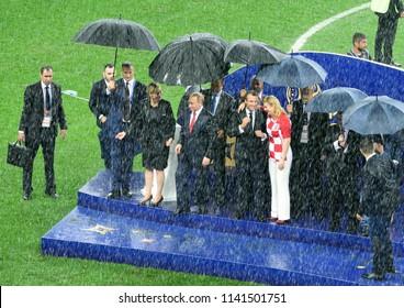 Moscow, Russia - July 15, 2018. Russian President Vladimir Putin, FIFA president Gianni Infantino, French president Emmanuel Macron, Croatia president Kolinda Grabar-Kitarovic in torrential rain.