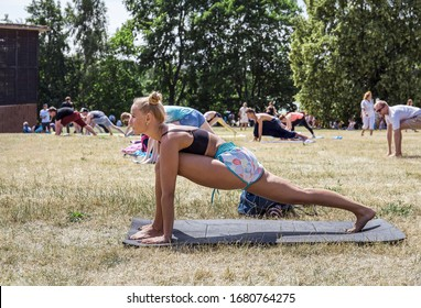 Moscow, Russia, July 18, 2019: a pretty blonde does yoga in the fresh air. Group yoga classes in the fresh air.