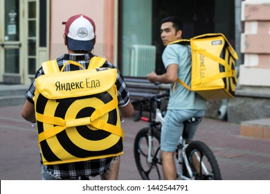 Moscow, RUSSIA - July 2, 2019, Food delivery in Moscow - courier in a hat with earflaps and a yellow jacket with inscription Yandex food and yellow backpack rides on bicycle on street
