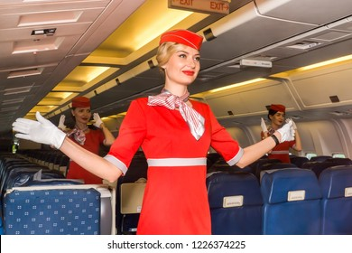Moscow, Russia - July, 2018: Charming stewardess dressed in uniform shows safety in the passenger cabin of the aircraft