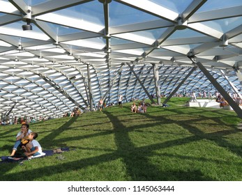 Moscow, Russia - July 2018: Tourists resting under the glass crust of summer amphitheater at park Zaryadye, new Moscow landmark